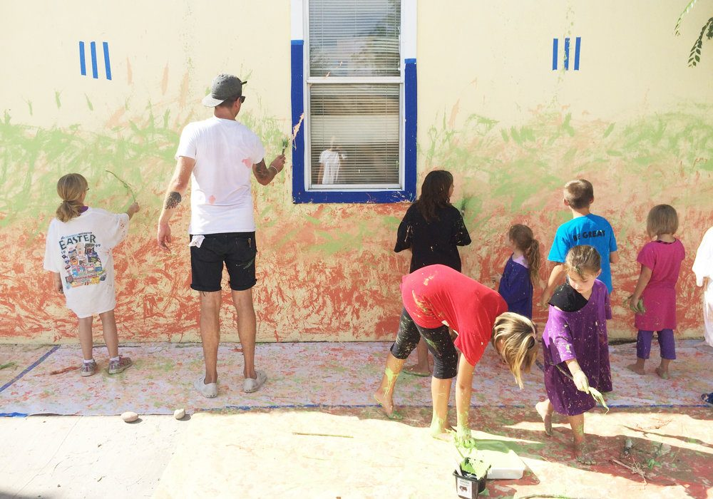 Corbin LaMont and Tom O'Toole painting a mural with kids from PACT